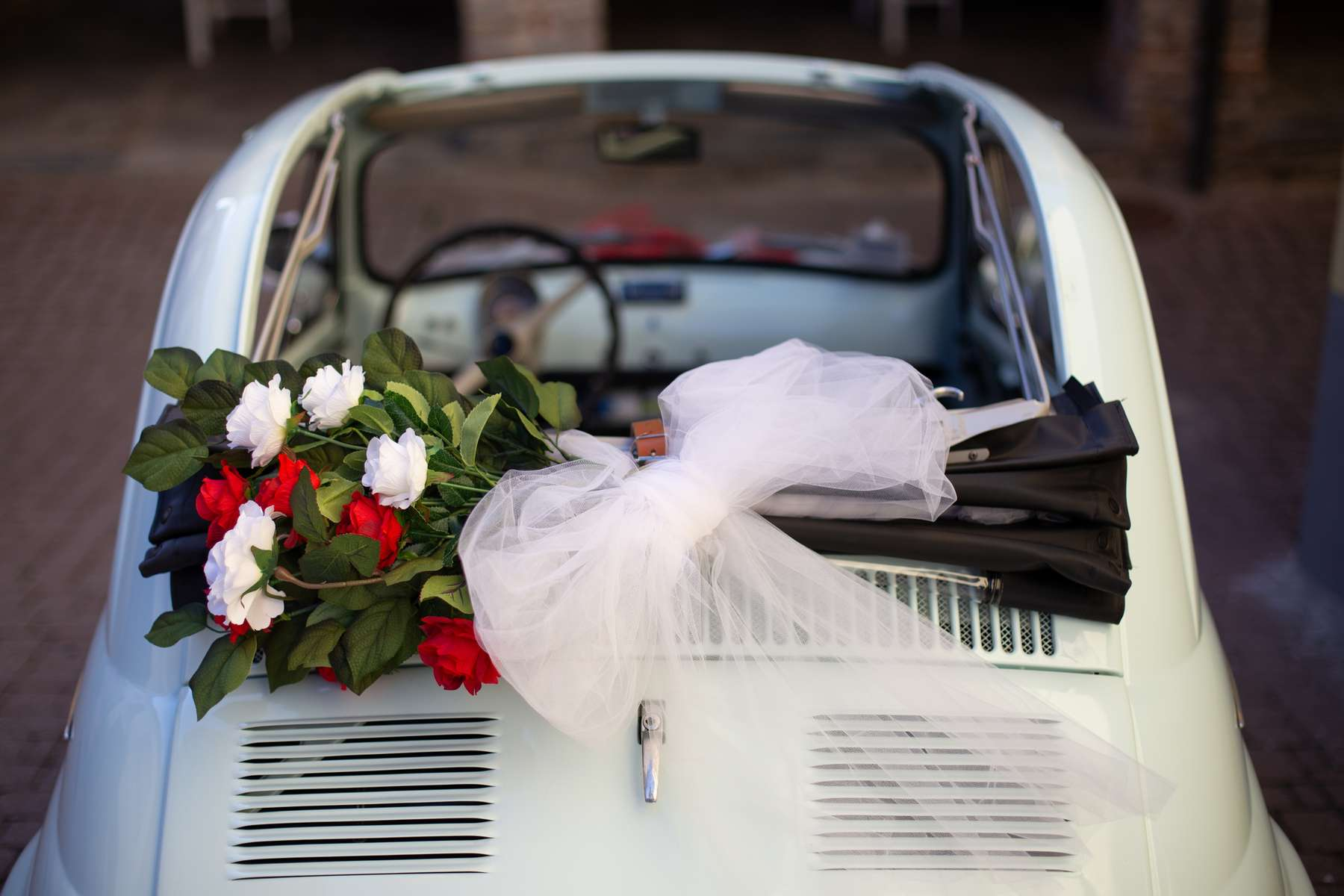 An overhead shot of bouquet of flowers placed at the top of the car with a blurred background